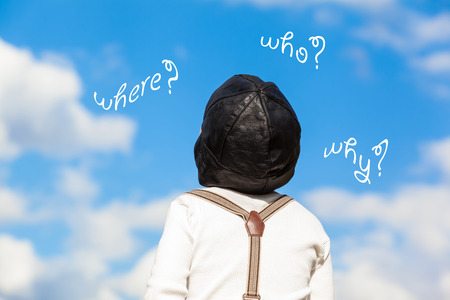 comprehend: Little boy in vintage clothes (grandad shirt, suspenders, pilot cap) looking up to the blue cloudy sky and ask questions (where, why, who) Stock Photo