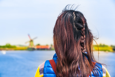 dutch girl: Back of a young girl with dark long hair and fashion accessories who is looking to nice dutch river landscape with an old windmill at the netherlands countryside Stock Photo