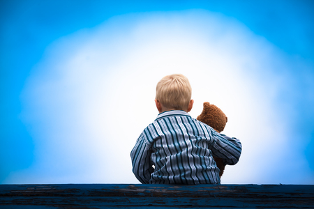 Little boy in pajama cloth sitting at a wooden roof with the teddy bear in his arm in front of a bright light at the dark blue sky Stock Photo