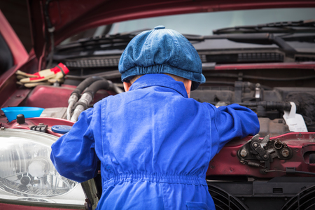 engine compartment: Little boy in blue workwear overall in front of open engine compartment doing some maintenance work at the car