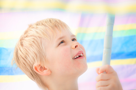 Cute child boy at school age with missing milk tooth smiling under pastel colored sunshade umbrella Stock Photo