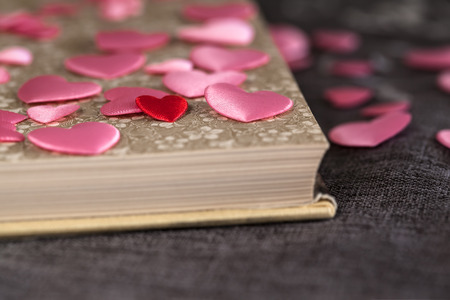 poetic: Detail of one very small red heart among many pink ones and open vintage book on brown textile surface (copy space) Stock Photo