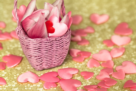 poetic: Basket with blossom and red miniature heart on vintage green pattern with many pink hearts Stock Photo