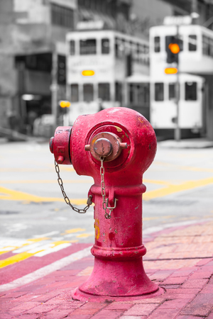 Vintage red fire hydrant at Hong Kong sidewalk and two streetcars at traffic background (color key)
