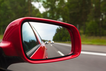 View back to road through red side mirror at car