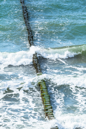 groynes: View from above down to row of groynes in waves of baltic sea