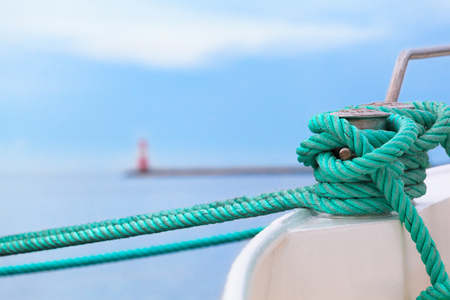 Green rope fix boat with knot at bollard in harbor - pier, lighthouse, open sea at background (copy space)