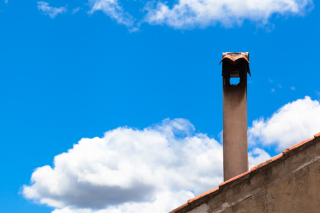 Detail of old roof with shingles and nostalgic chimney in front of blue sky background, white clouds (copy space)