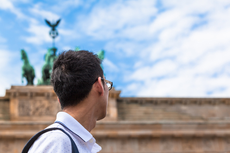 Young asian tourist or business man in Berlin (Germany) looking up to statue of Brandenburg Gate (copy space) 版權商用圖片