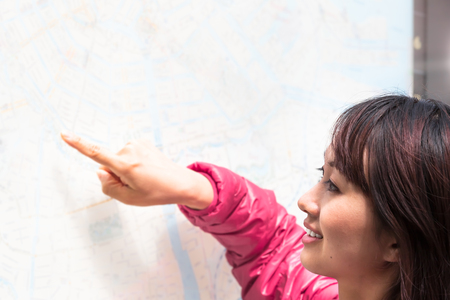Young smiling asian woman look and point a finger at bright city map board (copy space)