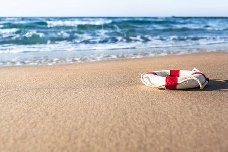 Bouée de sauvetage miniature rouge et blanc vintage sur la plage de sable de la mer baltique (espace de copie) Banque d'images