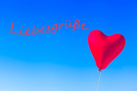 Flying heart shaped red helium balloon tied by rope at blue sky background and wavy german language textual message - LOVE GREETINGS (copy space)