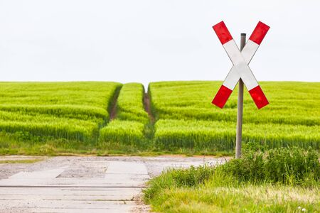 Unguarded railroad crossing with saltire sign at lonely rural way, no train passing, green agricultural field in spring (copy space) Standard-Bild