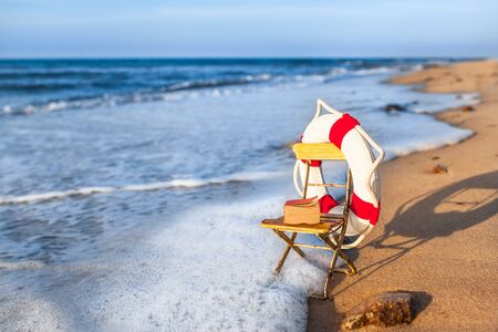 Vintage vacation scene miniature garden chair at beach shore wave, decorated by nostalgic life buoy and book