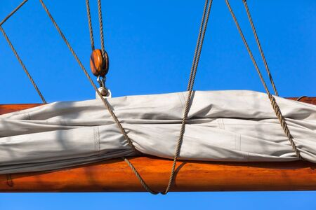 Detail of pulled in canvas sail at wooden sailship with ropes and rigging (copy space) 스톡 콘텐츠