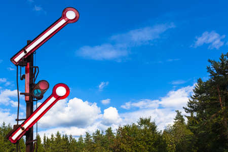 Old nostalgic go ahead railway signal at nature above treetops and blue sky background for your text (copy space)