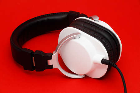 Modern black and white headphones with cables isolated on red background. Banque d'images