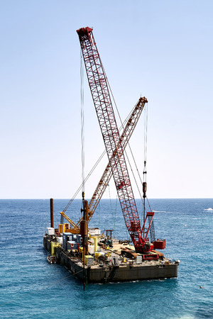 platform floating in open sea with two heavy cranes