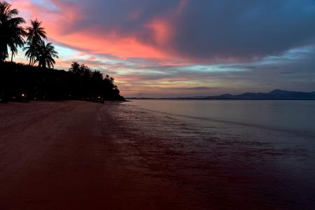 atardecer en la playa tailandesa con palmeras en colores azul y rojo