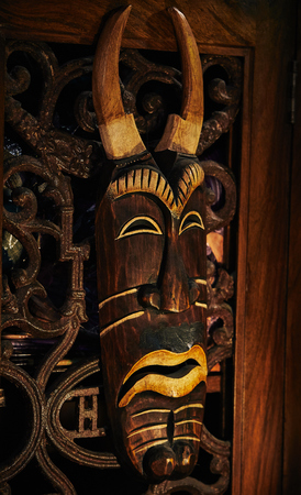 wooden voodoo mask and  lizard on the background of a wooden door on metal hinges