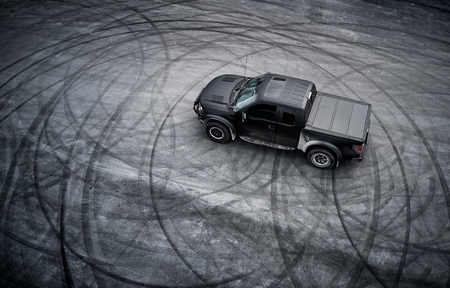 big black matt American pickup truck staying after drifting on the asphalt with tire marks