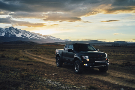 Big American pickup truck Raptor rides on the Kurai steppe at sunset. Glaciers and Altai Mountains in the background and a beautiful cloudy sky.