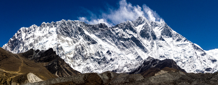 Front view of south face wall of Lhotze and nuptse mountain in Nepal. Hymalayas.  8516 meters above the sea. with clouds above it. at sunny day.