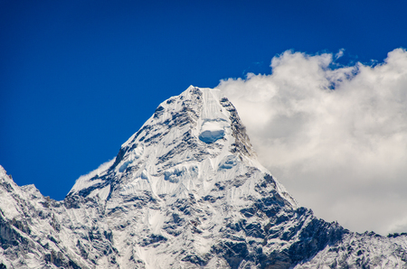close look beautiful view of Ama Dablam from trek to Everset and a clouds in a sunny day near the summit.