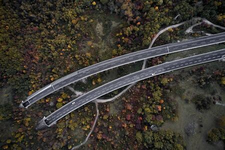 High autumn alpine speed road in Italia with exit or enter into the tunnel. Aerial view from above. Imagens