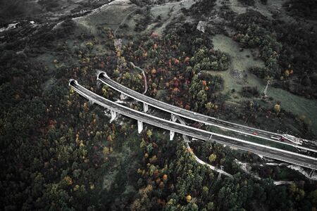 High autumn alpine speed road in Italia with exit or enter into the tunnel. Aerial view from above. 版權商用圖片