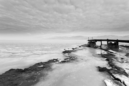 wooden jetty in the frozen lake photo