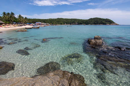 The crystal clear waters of Pulau Perhentian Kecil with the beach and head lands in the back ground. Stock Photo