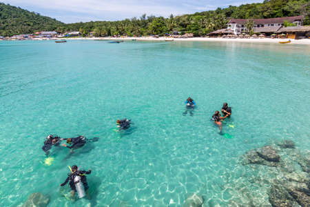 A group of Scuba Diving students have a lesson in the shallow crystal clear water of a Tropical Island.