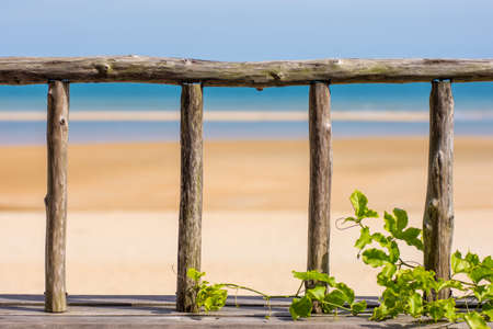 An old weathered wooden fence bannister with a backdrop of a golden sand beach and beautiful blue sea.