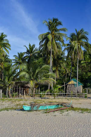 A basic Filipino pump boat on the shore of a white sand beach with a back ground of fenced area, palm trees and a basic bamboo hut. Stock Photo