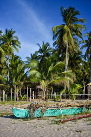 Depth of field shot of a basic Filipino pump boat on the shore of a white sand beach with a back ground of fenced area, palm trees and a basic bamboo hut.
