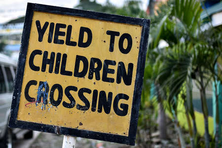 A hand made wonky Yield to Children sign in yellow and black.