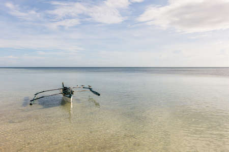 A Filipino fishermans basic pump boat floating empty on a still calm tropical sea with seagulls resting on its stabilizers.