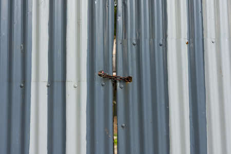 Painted corrugated metal gate padlocked shut with a rusty heavy duty metal chain.