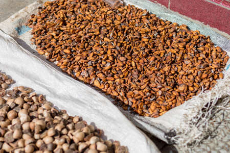 Cocoa beans other spices drying out in the street in the midday sun.