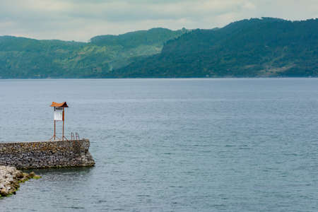 Stone jetty pier with welcome sign jetting out in to a crater lake with jungle covered hills in the back ground. Stock Photo