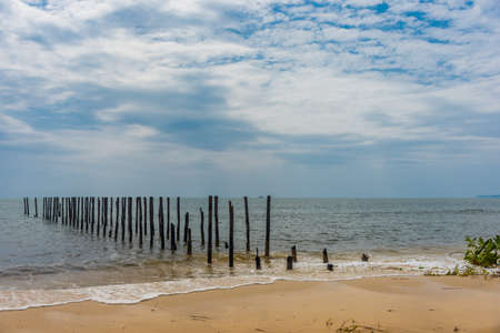 uninhabited: Rows of wooden posts go out in to a calm paradise sea off of a beautiful paradise beach in Cambodia.