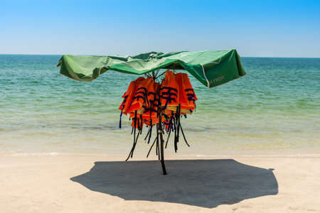 lifevest: Personal floatation devices protected from the sun under a parasol on an empty paradise beach. Stock Photo