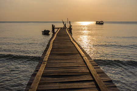 A wonky wooden jetty pier goes out in to a calm sea with small boats around with golden hour lighting. Stock Photo