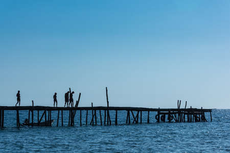 A silhouetted group of friends walk along an old wooden pier over a blue sea and in front of a blue sky. Stock Photo