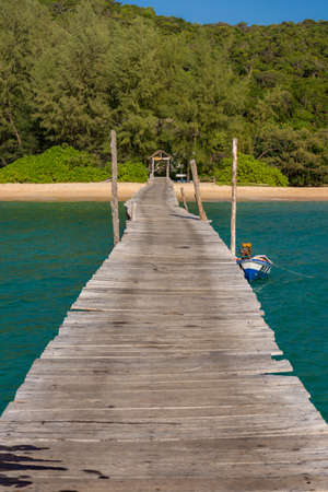 Old wooden pier leading to white sand beach lined with dense forest. Stock Photo