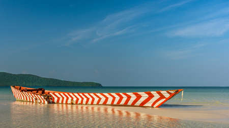 Old Red and White wooden boat left to rot on a white sand beach in a tropical beach bay. Stock Photo