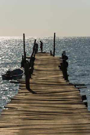 Two people at the end of a wonky wooden jetty.