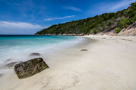 uninhabited: Long exposure of waves from tranquil sea on to tropical white sand beach with tree covered hill background and blue skies. Stock Photo
