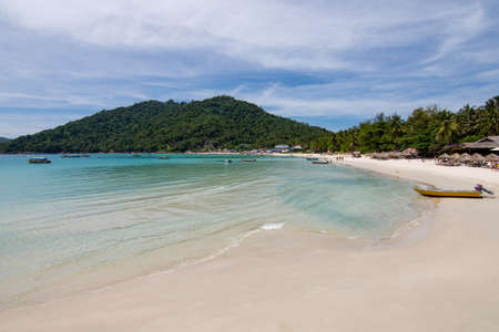 Paradise beach view with huts and small boat and a forested hill background. Perhentian Kecil, Malaysia.